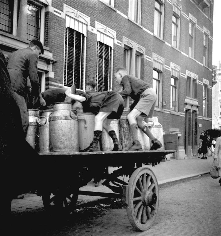 Kar met jongens die de melkbussen met voedsel uitschrappen.